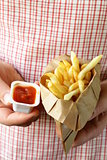 paper bag with potatoes french fries and ketchup in the hands