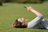 Woman using a smart phone resting on the grass in a park