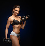 Smiling athletic woman pumping up muscles with dumbbells