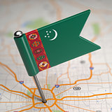Turkmenistan Small Flag on a Map Background.