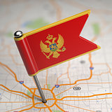 Montenegro Small Flag on a Map Background.