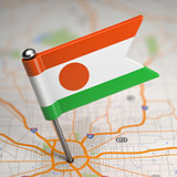 Niger Small Flag on a Map Background.