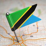 Tanzania Small Flag on a Map Background.