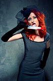 Gorgeous redhead woman with bloody knife in her hand