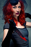 Redhead woman with blood on her lips and bloody knife in hand