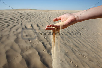 Woman hand in the sand