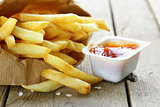 Traditional potatoes French fries with salt on wooden background