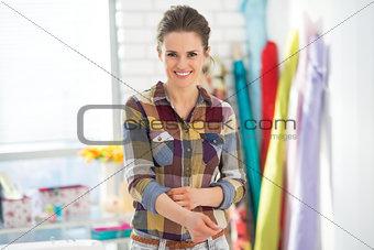 Portrait of smiling seamstress in studio