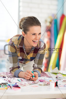 Portrait of laughing seamstress in studio