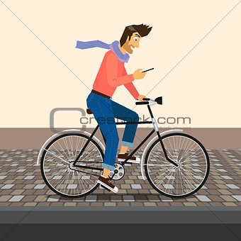 Handsome guy is riding a bike and sending a message in smartphone