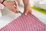 Closeup on seamstress cutting fabric