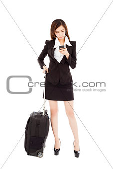 business woman watching smart phone with her  baggage