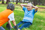 asian senior grandfather doing sit-ups in the park