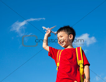 little boy holding a airplane toy with a backpack
