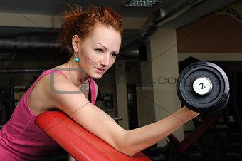 Slim girl doing biceps training