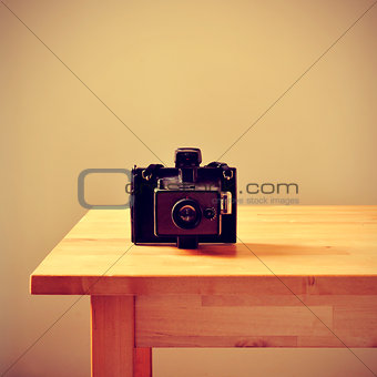 old instant camera on a table, with a retro effect