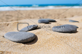 gray flat stones on the sand of a beach