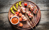 Grilled bacon skewers with chicken, peppers and cherry tomatoes