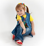 little girl in jeans and sandals is sitting on the floor