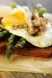 Toast with egg, green asparagus and turkey on the old board..