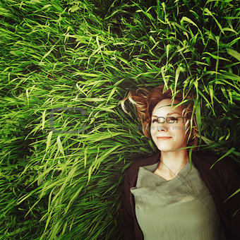Beautiful young woman lying in the grass. Instagram retro effect
