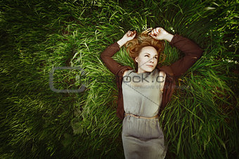 Beautiful young woman lying in the grass. Retro colors. Summer.