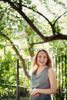Beautiful laughing young woman in the park. Summer, wind.