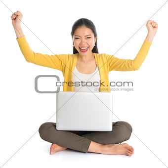 Asian girl arms up using laptop computer