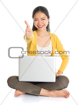 Asian girl using laptop pc and thumb up