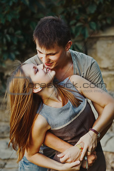 Teen couple bonding, posing together, looking at camera.
