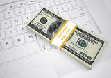 Bundle of dollar bills lying on computer keyboard