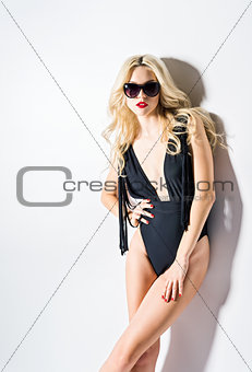 Studio fashion shot: beautiful young woman in swimsuit and sunglasses