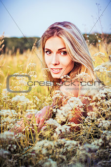 Beautiful smiling young girl sitting among the grass and flowers