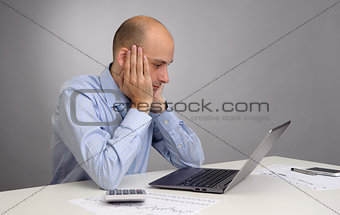 Tired businessman working with laptop in the office