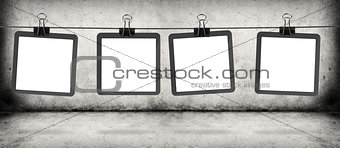 frames on the rope hanging over gray concrete wall and floor