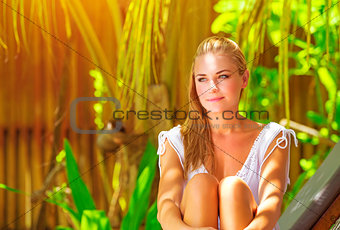 Beautiful woman sitting in tropical park