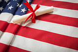 Ribbon Wrapped Diploma Resting on American Flag with Copy Space