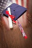 Graduation Cap and Diploma on Table with American Flag Reflection