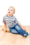 Cute little boy sitting with teddy bear and book isolated