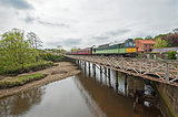 English train on traveling on bridge over a river