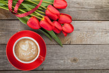 Fresh red tulips with ribbon and coffee cup with heart shape