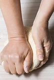 Hands kneading a dough.