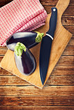 Eggplant or Aubergine with knife on wooden chop board