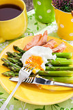 Breakfast with poached egg and green asparagus