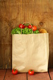 paper bag with food, lettuce, tomatoes, bread on a wooden background