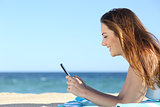 Profile of a woman texting in a smart phone on the beach