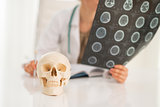 Closeup on human skull and medical doctor woman with fluorograph