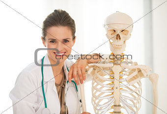 Portrait of smiling medical doctor woman near human skeleton ana