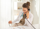 Smiling medical doctor woman talking phone