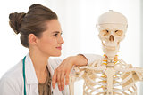 Portrait of medical doctor woman looking on human skeleton anato